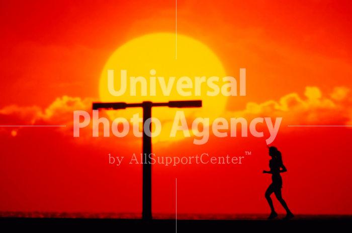 ハワイ 夕日とともにランニングする女性 / hi01-9